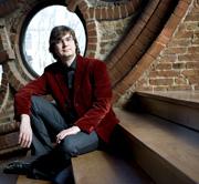 Stephan Graf v. Bothmer sitzt auf eine Holztreppe in einem alten Steingebäude